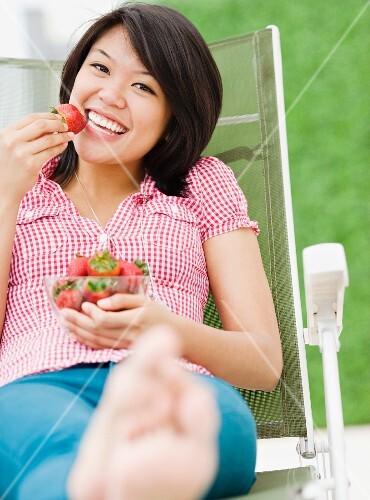 Asian woman eating strawberries