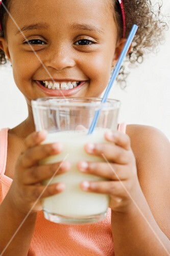 Mixed race girl holding glass of milk