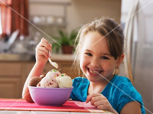 Caucasian girl eating bowl of ice cream