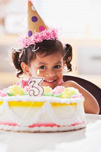 Happy Hispanic girl sitting with birthday cake
