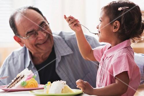Hispanic girl and grandfather eating birthday cake