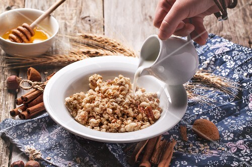 Plate of muesli with pouring milk, cinnamon and nuts over old wooden background