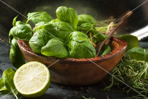 wooden bowl of fresh basil and half of lime over dark bakground