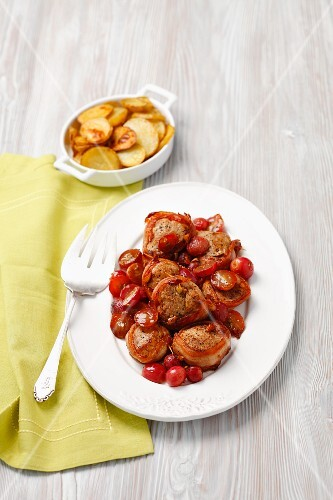 Pork fillet wrapped in bacon with grapes and a side of potatoes