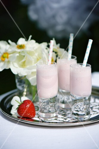 Strawberry milkshakes in small glasses with straws on a silver tray