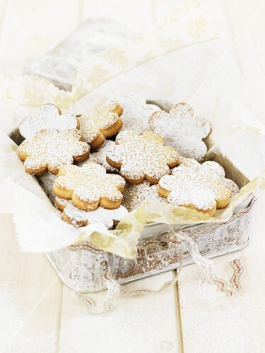 Flower-shaped biscuits with icing sugar in a biscuit tin