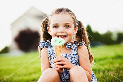 A girl sitting in a meadow holding an ice cream cone