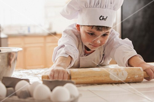 A boy wearing a chef's hat and tunic, rolling out pastry