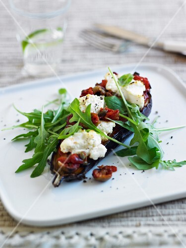 Baked aubergine topped with sundried tomatoes, mozzarella and rocket