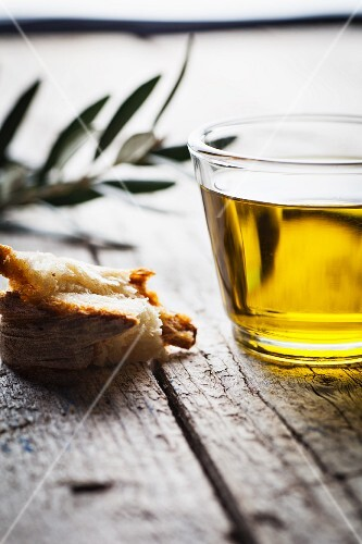 Olive oil, a piece of bread and an olive twig