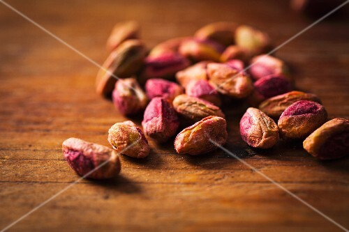 Shelled pistachios on a wooden surface