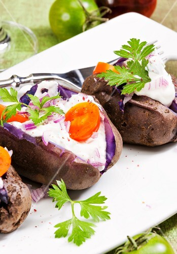 Purple baked potatoes with sour cream, onions and tomatoes