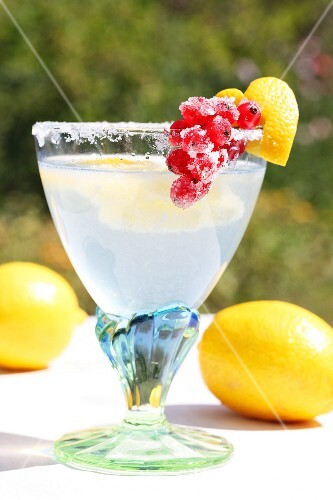 'Cold Duck' punch in a glass with a sugared rim, decorated with a heart made from lemon peel and with candied redcurrants