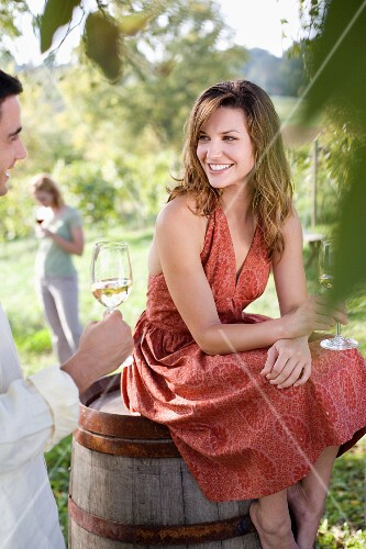 Woman Sitting on Barrel Talking to Man at Party