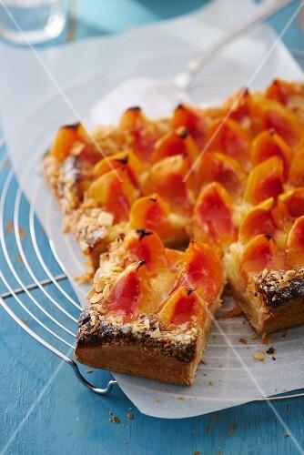 Peach tart, part, one slice cut, on a wire rack
