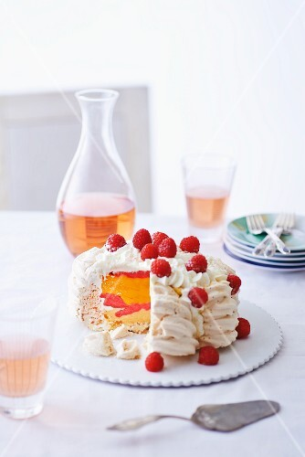 Meringue torte with Vacherin cheese and raspberries, partly sliced