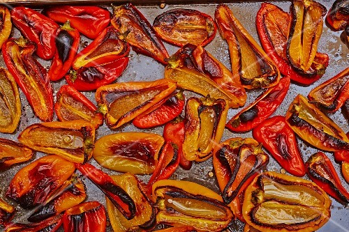 Baked red and yellow peppers on a baking tray