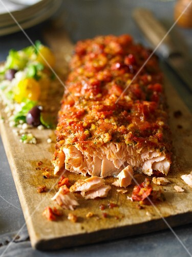 Baked salmon with crisp topping on a chopping board