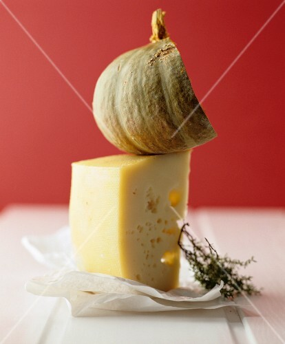 A still life featuring Mondseer cheese, squash and a sprig of thyme