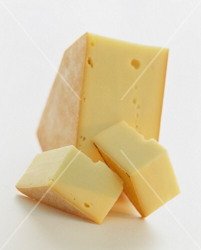 A wedge of Raclette cheese against a white background
