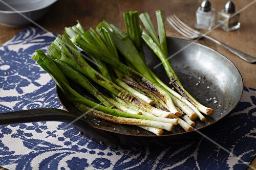 Caramelised spring onions in a frying pan