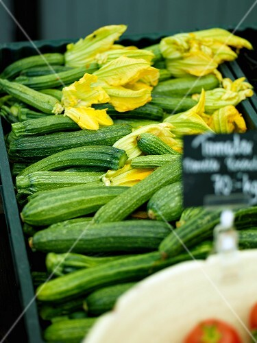 Fresh courgettes, some with flowers, in a crate on a market stall