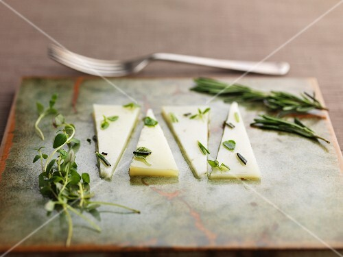 Slices of Manchego cheese with rosemary and oregano