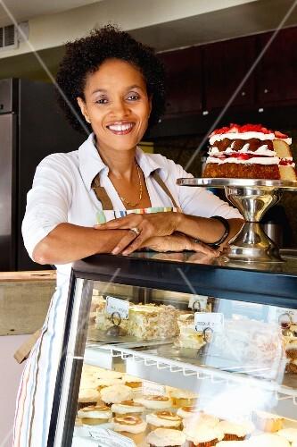 Frau bei der Kuchenvitrine in einer Konditorei