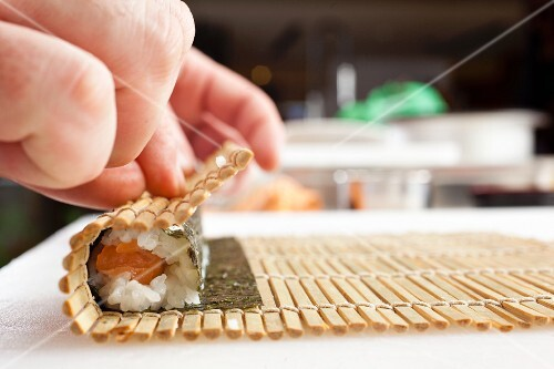Maki sushi being rolled up using a bamboo mat