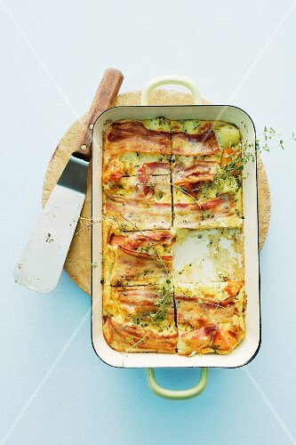 Spanish omelette with rashers of bacon in a casserole dish
