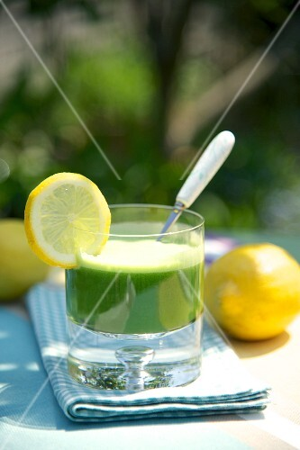 Spinach and lemon drink with slices of lemon, on a table in the garden