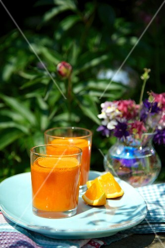 Two orange and carrot drinks on a table in the garden