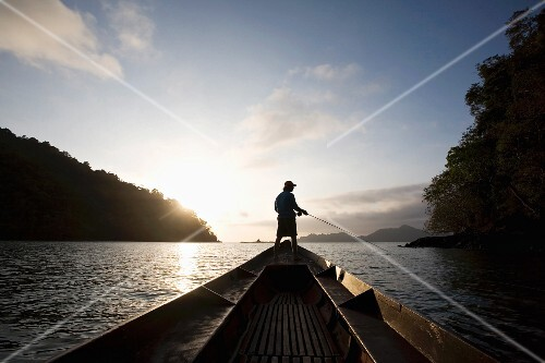 Silhouetted Man Fishing on Boat at Sunset