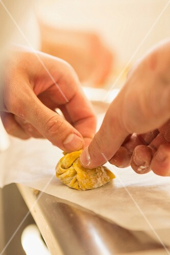 A tortellini being folded together