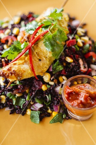 Chicken skewer with coriander leaves on black rice salad