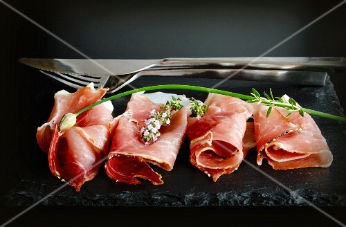 Rolled slices of Black Forest ham on a slate slab with chives