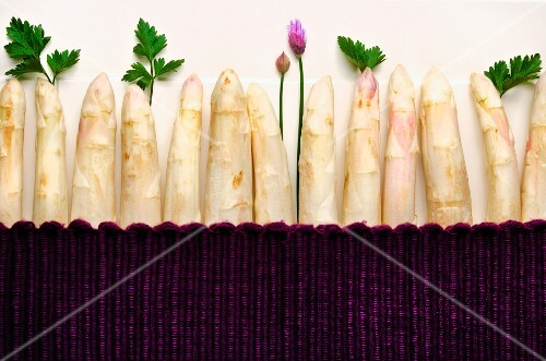 Stalks of white asparagus with parsley and chives