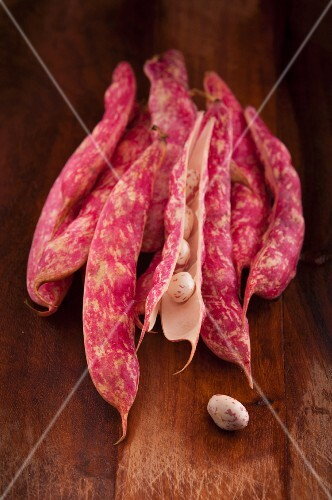 Borlotti pods and beans on wooden cutting board
