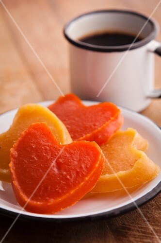 Heart-shaped candies of pumpkin (orange) and sweet potato (yellow) with cup of coffee on the background