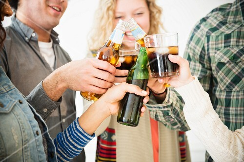 Young people at a party clinking glasses together