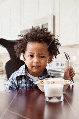 Afroamerikanischer Junge sitzt vor Schale mit Cerealien