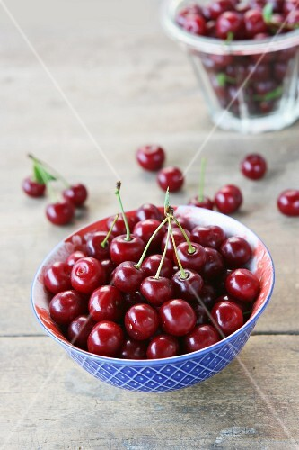 Fresh cherries in a blue and white bowl on a wooden surface