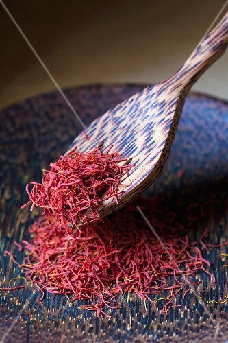 Saffron threads on a plate with a wooden spoon