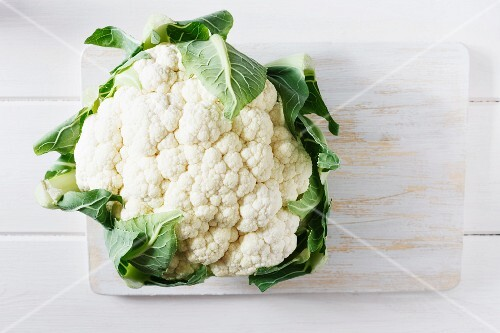 A cauliflower on a chopping board (view from above)