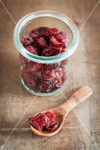 Dried cranberries in a jar and on a wooden spoon