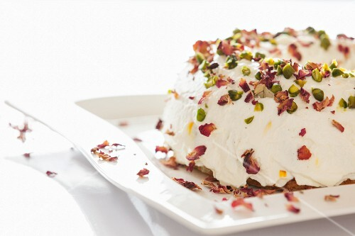 A Bundt cake with white icing, pistachios and rose petals