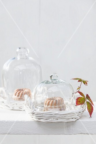 Mini iced Bundt cakes under glass cloches
