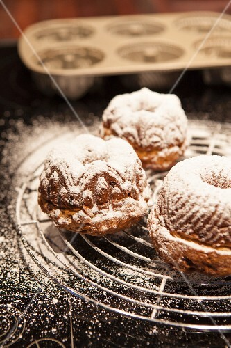 Christmas Bundt cakes dusted with icing sugar on a wire rack