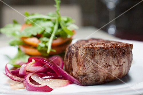 sirloin steak with red onions, tomatoes and rocket leaves