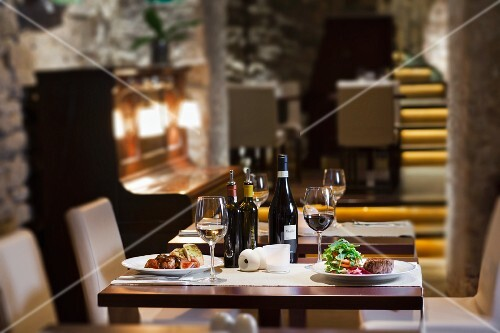 a view on the interior of the restaurant, a table set for two with wine, a dish of sirloin steak with red onions, tomatoes and rocket leaves and a dish of grilled liver with figs